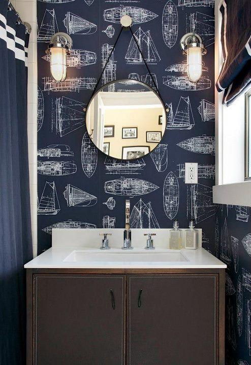handsome seaside bath, nautical wallpaper, round mirror, beachhouse style, industrial sconces, boys bathroom