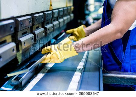Asian worker in factory at metal skip machine putting work piece in - stock photo