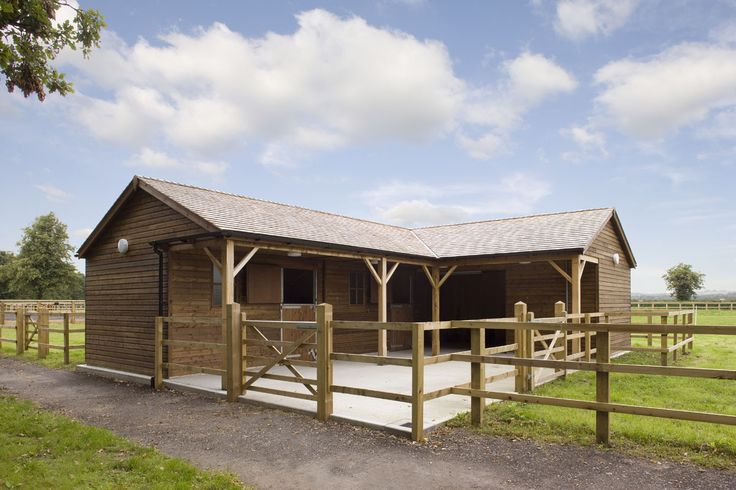 Two stables with oak beams, open store and tack room. Designed and built by The Stable Company for a client in York, England.