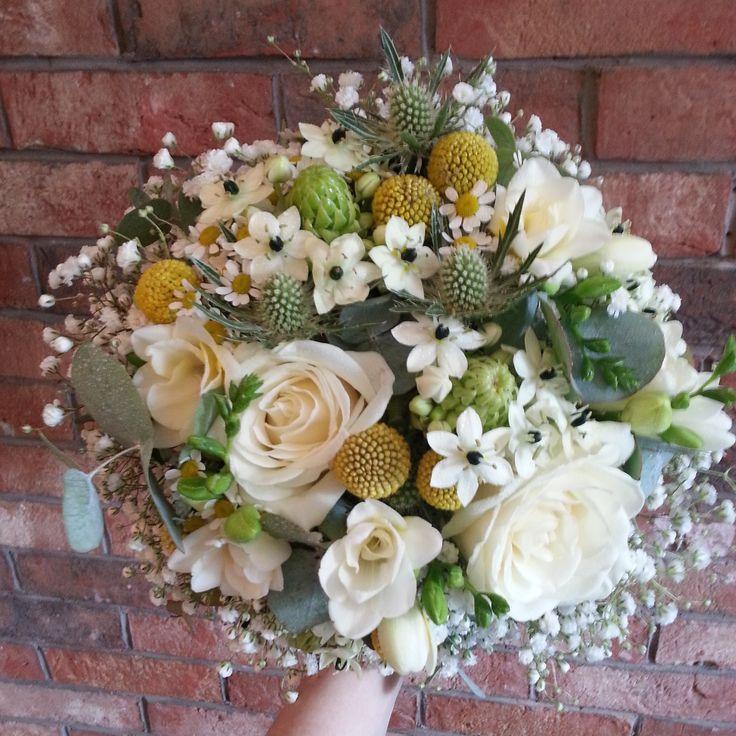 Beautiful springlike bouquet, including craspedia, avalanche roses, ornithogalum, thistle, freesia and gypsophila.