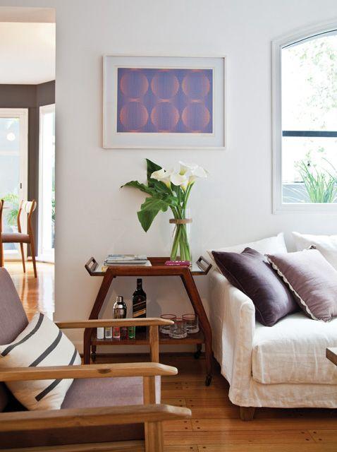 Living cálido y vintage de un departamento con piso de madera, sillones individuales modelo Andino y mesita-bar de los años 50 con espejo biselado de Mesopotamia.
