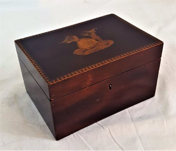 We are offering is adorable Vintage Mahogany Box with an Inlaid Wood Dancing Couple on the top. This box would be perfect to get your personal items and trinkets. I could imagine its original owner keeping love letters in it! This piece is has such an exquisite look. The mahogany color is beautiful. The two dancers are made of different woods, with each piece of their body, clothing and so forth, inlaid individually. The boreder around the top is also inlaid wood. This little trinket box is…