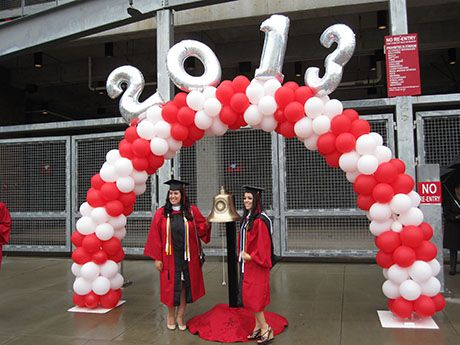 Outside the stadium under a red and white balloon arch with 2013 in large silver balloons, graduates rang the Red Lion Bell announcing their arrival in a tradition connecting every graduating class back through the first classes in the 1770s.