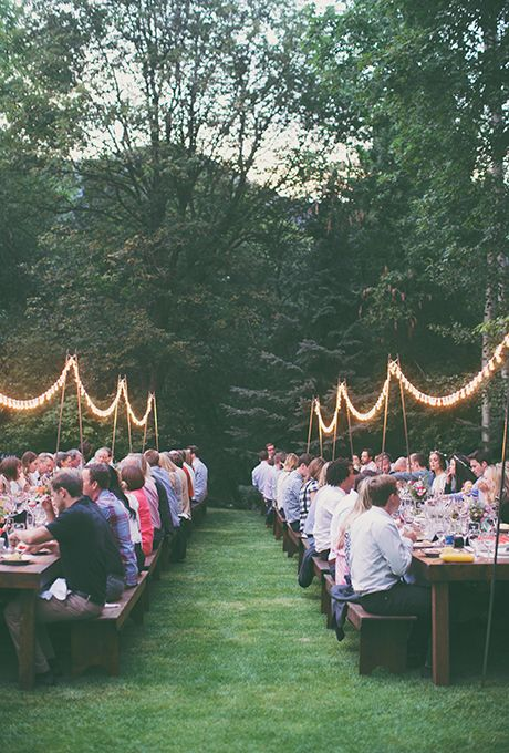 Brides.com: . Create a casual vibe for your backyard reception with long picnic tables and twinkly lights hanging overhead.