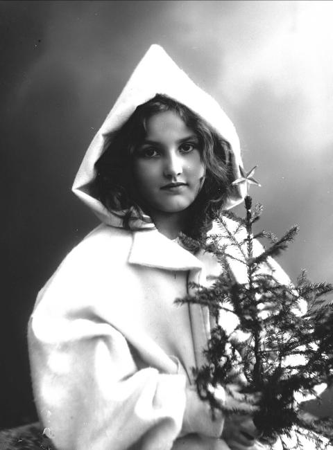 Girl with a small christmas tree. Photographed between 1895-1907.Photo: Solveig Lund/Norsk Folkemuseum