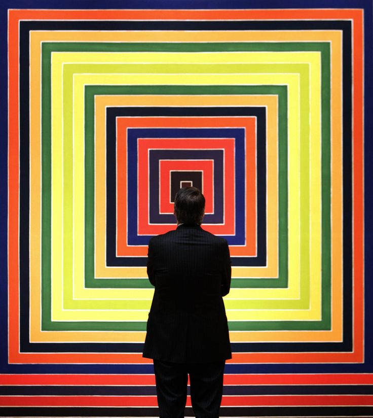 "A member of the public walks past the painting ""Jacques le Fataliste"" by Frank Stella. Courtesy of Getty Images."