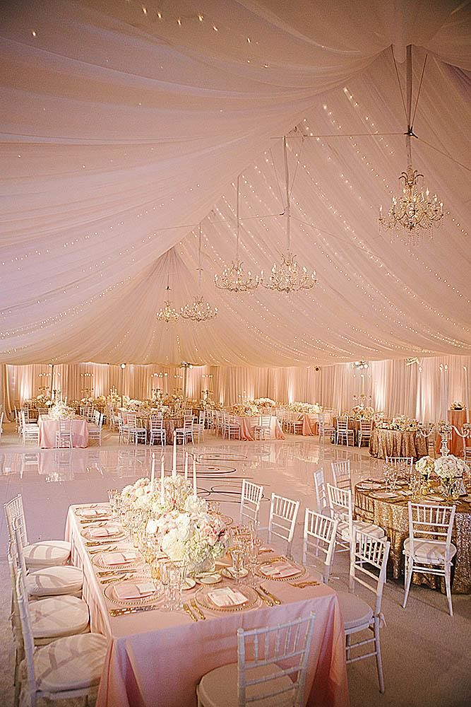 rose gold wedding decor reception under a pink tent with elegant chandeliers and lights on tables gold tablecloths and flowers chairs white josh elliott