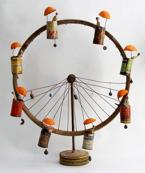 I could make something like this out of an old bicycle tire and tin cans.  Would make a super cute yard ornament.