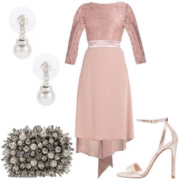 Il vestito color rosa cipria, con bustino in pizzo che lascia le spalle scoperte, ha le maniche a 3/4 e la cintura in raso chiusa sul dorso da un elegante fiocco con nastri lasciati liberi. Sandali alti in ecopelle effetto madreperla, tacco a spillo e cinturino alla caviglia. La pochette con applicazioni di perle, strass e brillantini rappresenta il gioiello principale del look, accompagnata dai semplici orecchini a lobo con perline e strass.