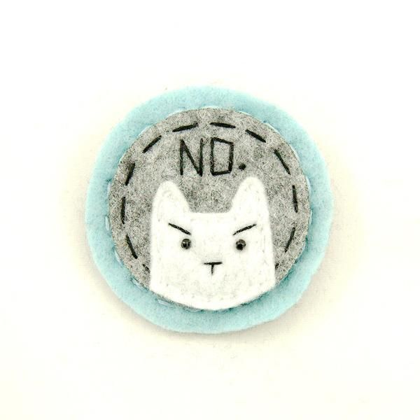 Lumpy Buttons handmade felt brooches are amazingly cute and kitschy! This round brooch pin has a white kitty with NO stitched in black on a light blue and gray background. Mounted to a straight bar pin. Measures 2 inches, lightweight and made in the USA. Collect them all!