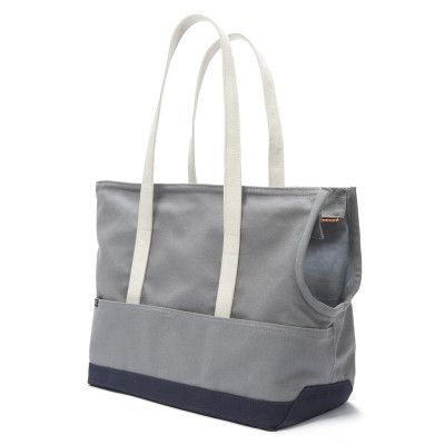 Abbott Canvas Dog Carrier Tote - Grey & Navy Casual, preppy and cool, this smart tote is one of our favorite dog purses. Hand-crafted of the finest materials in Brooklyn, New York, the tote features cotton duck canvas with double topstitching for ultimate durability—and a water-resistant finish to protect your pooch from the rain. A scoop opening forms the perfect place for your furry friend to rest their head, while two outer pockets promise to hold all your essentials.