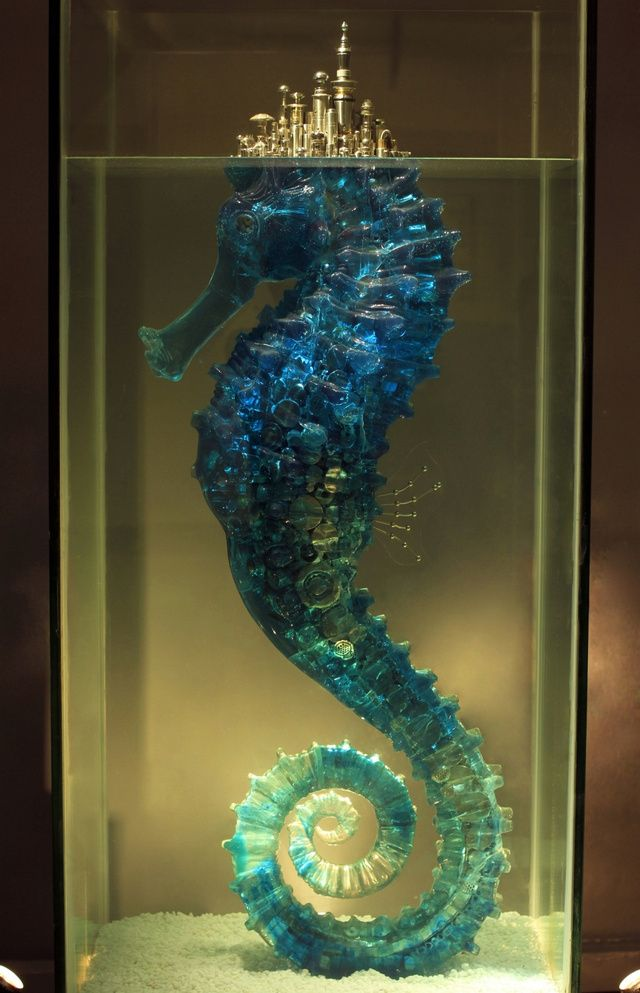 """From io9: Chinese sculptor Hu Shaoming. Hu explains that the seahorse piece, titled """"City of Dreams,"""" is actually about the broken nature of its fairy tale premise, the idea that nature is supporting humanity's urban dreams, and will one day be exhausted. The golden series, his """"Umbrella"""" series, contains by his count 2,000 individual buildings, made of metal from buttons, clothing accessories, utensils, food containers, furniture fixtures, and other odds and ends of daily life."""