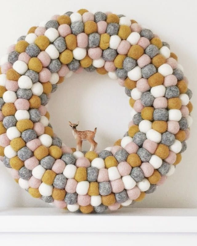Looking for simple holiday decor? We love this darling wreath with a little deer and a million pompoms. Add sweet little wooden mushrooms to complete the winter scene.