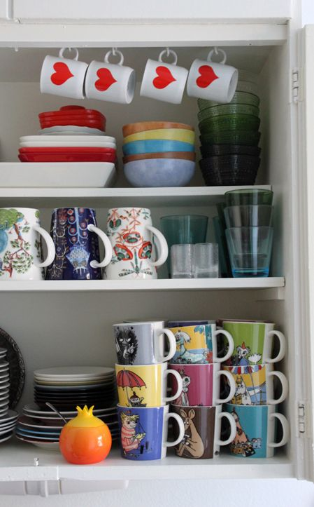 "My colorful kitchen cupboard. Heart cups > flea market finds. Square plates > ""Teema"" by Iittala. Hand-painted bowls > made by my great aunt. Glass bowls > ""Kastehelmi"" by Iittala. Large mugs > by Iittala, illustrator Klaus Haapaniemi. Shot-glasses > ""Mini"" by Iittala, designer Tapio Wirkkala, from flea markets and antiques shops. Glasses > ""Kartio"" by Iittala. Plates > mostly flea market finds, smallest ones ""Teema"" by Iittala. Sugar bowl > by Alessi. Moomin-mugs > by Arabia."
