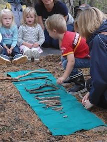 A simple game of sticks can teach alot. Everyone searches for a stick, then take turns to lay it on a cloth with the outcome (hopefully) of sticks growing in size down the line