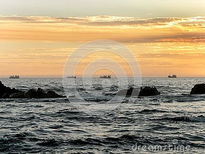 A view of the sun setting over a beach in South Africa with fishing boats in the background.