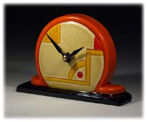 Astoria Mantel Clock. Height 9cm by 14cm Wide. £55. A modern interpretation of Art Deco.  	 The Idea for this unique timepiece comes from creatively combining distinctive Art Deco lines with the attractive elements of British Interior Design from the 1920's and 30's. This piece has been finished in Amber Sunrise glaze with Black & Mottled Green highlighted detail.