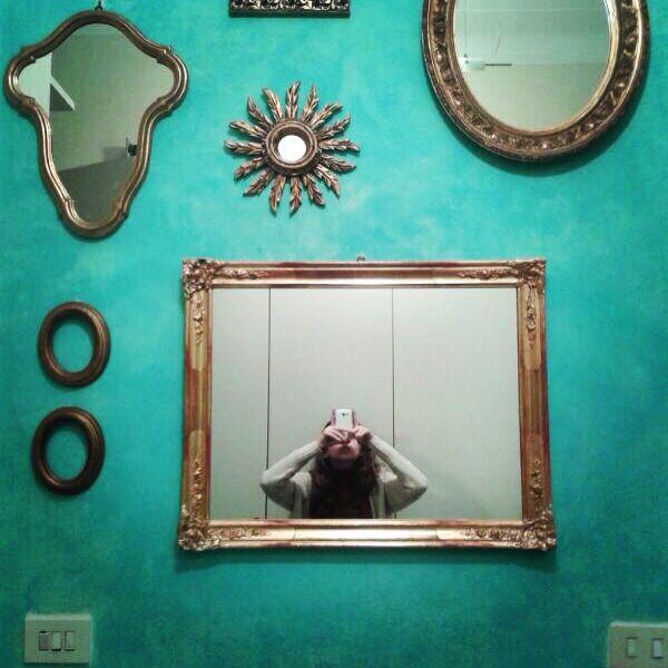 # parete turchese con cornici e specchi dorate.