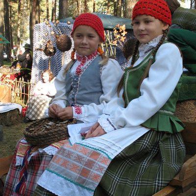 Lituania, Lietuva: Los trajes masculinos y femeninos utilizan una variedad de colores, diseños, texturas y patrones. Las mujeres usan delantales bordados con diseños geométricos cubren las faldas de tela escocesa largas, sombreros adornados con cintas y chalecos son también elementos típicos lituanos a los trajes tradicionales. La ropa de los hombres, mientras que sobrio, está decorada con fajas tejidas y botas.