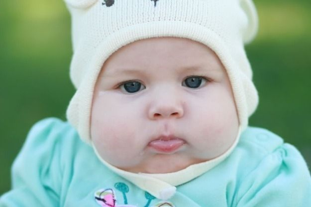 Her hat can barely contain those adorable cheeks.