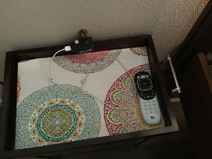 Small tray table with coordinating fabric is the perfect charging station and place to keep tv remote and reading glasses