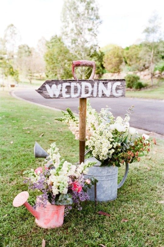 Cute idea for a country or garden wedding. I love the use of the pitchfork as the sign post and watering cans as flower holders. #WeddingSignage #Decor #ThisWay