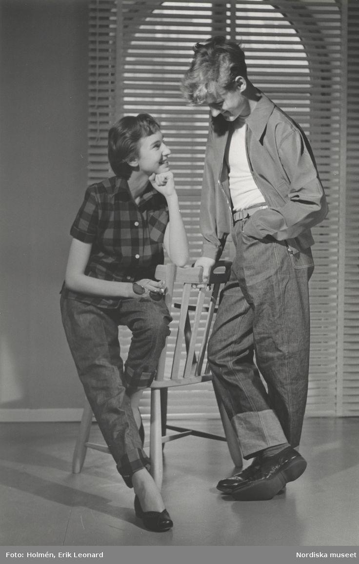 Tonårsmode. Tjej i rutig skjorta och jeans från Melka sitter på en stol. Kille i poplinjacka, vit t-shirt och jeans står bredvid. Fotograf: Erik Holmén, 1953.