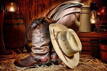 cowboy western: Ouest américain cowboy de rodéo traditionnel chapeau de paille blanc reposant sur des bottes de travail du cuir Roper éleveur avec d'authentiques occidentaux éperons d'équitation et des gants dans une grange ranch vintage avec antiques fournitures élevage éclairé par les lampes au kérosène anciens nostalgiques de pétrole lanterne