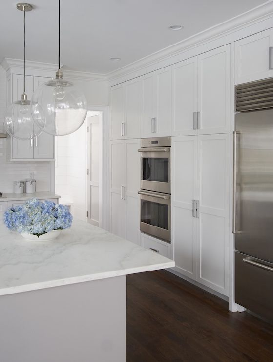 Beautiful kitchen features a wall of floor to ceiling pantry cabinets fitted with double ovens and an under cabinet refrigerator.