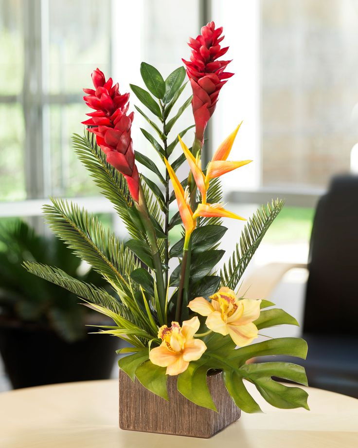 "An arrangement from your favorite island paradise. Tropical flowers and foliage so lifelike, they will fool even a discerning eye. Natural colors of torch ginger, bird of paradise, heliconia, and cymbidium orchids amid lush tropical greenery capture the botanical beauty of the islands for your home and office. It's designed in a bronze tone 6"" square ceramic container."