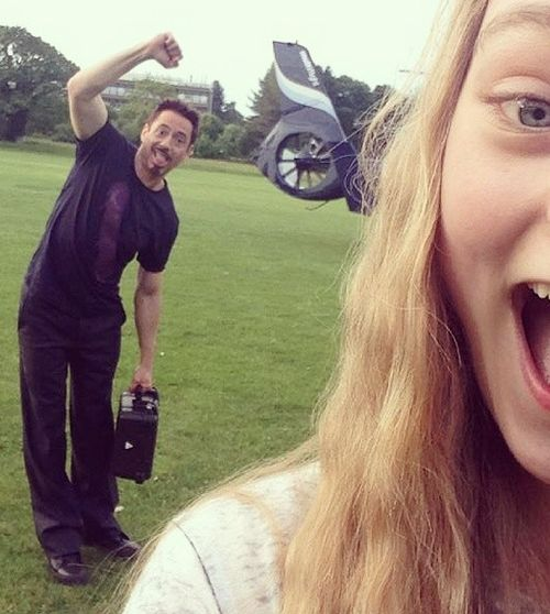 "Robert Downey Jr. hilariously photobombs this girl's selfie.  He was filming scenes on June 13, 2014 for ""Avengers: The Age of Ultron"" in Norwich, England."