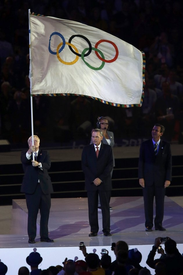London mayor Boris Johnson (L) holds the Olympic flag next to International Olympic Committee President Jacques Rogge (C) and Rio de Janeiro mayor Eduardo Paes during the closing ceremony of the London 2012 Olympic Games at the Olympic Stadium August 12, 2012. REUTERS/Sergio Moraes