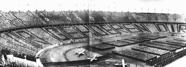 """Em uma cerimônia durante os Jogos Olímpicos de 1936, espectadores alemães exibem a frase direcionada a Adolf Hitler, """"Wir gehoeren Dir"""" (Nós pertencemos a você). Berlim, Alemanha, agosto de 1936."""
