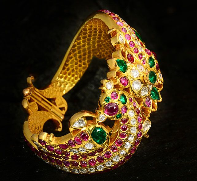 Fish Bangle in 22 karat gold studded with rose-cut diamonds, rubies and emeralds.