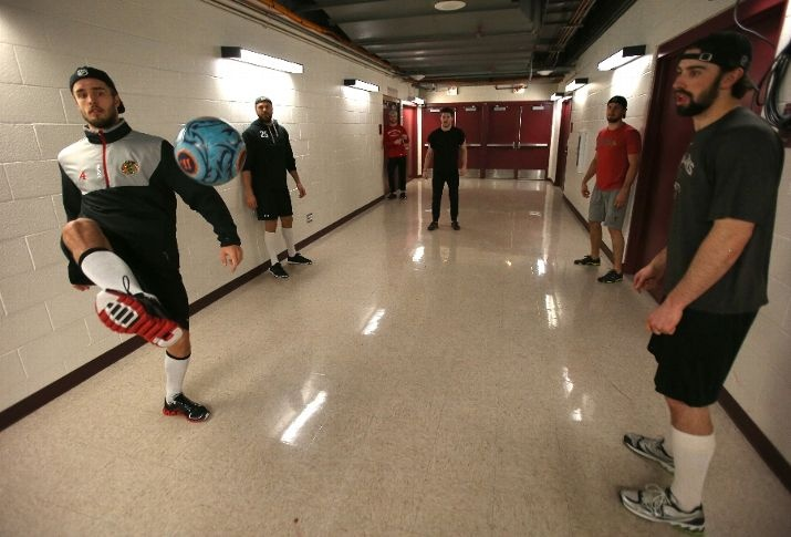 CHICAGO, IL - JUNE 02: Niklas Hjalmarsson #4 of the Chicago Blackhawks volleys a soccer ball in a hallway at United Center to teammate Nick Leddy #8 (far right) prior to Game Two of the Western Conference Final between the Los Angeles Kings and the Chicago Blackhawks during the 2013 NHL Stanley Cup Playoffs on June 2, 2013 in Chicago, Illinois. (Photo by Jonathan Daniel/Getty Images)