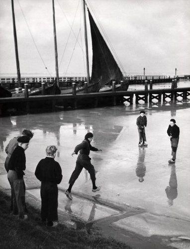 Een paar jongens met klompen aan begeeft zich op gevaarlijk ijs in de haven van Marken. Nederland, 1953. Op de achtergrond vissersboten