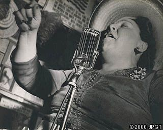 Singer, Sammy's Bar, New York,  Lisette Model from the September 1944 Harper's Bazaar. Taken from below and at a slight diagonal angle, the image captures the vitality and vibrancy of a local favorite in the Bowery district of New York, The angle from which the photograph was made also emphasizes the gleaming microphone, which seems to rise up to meet the challenge of projecting Tillie's already powerful voice.