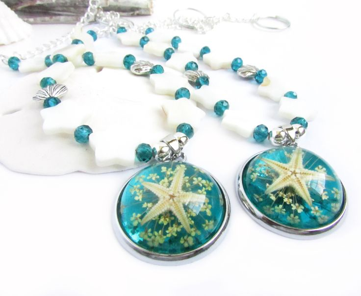 """This set of curtain tiebacks have a center focal resin starfish focal pendant. The tiebacks feature white shells in star shapes along with teal crystal beads and 2 silver tone shell charms.    The beautiful center resin pendant with a real starfish measures 38mm(1 4/8"""") x 31mm(1 2/8"""")    These ad..."""