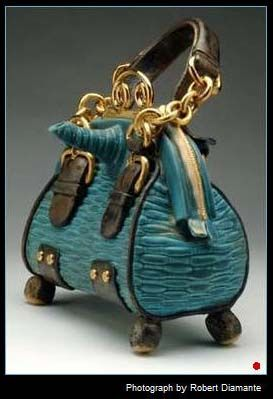 Turquoise Tea Tote is a ceramic teapot with a blue leather purse design.