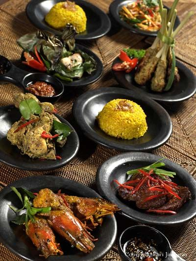 "The Indonesian rijsttafel,a Dutch word that literally translates to ""rice table"", is an elaborate meal adapted by the Dutch from the Indonesian feast called nasi padang.It consists of many (forty is not an unusual number) side dishes served in small portions, accompanied by rice prepared in several different ways. Popular side dishes include egg rolls, sambals, satay, fish, fruit, vegetables, pickles, and nuts."
