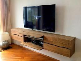 Zwevend tv-meubel van massief eiken planken. Een heel andere uitstraling dan je van ons gewend bent. Wel een strak maar geen rechtlijnig meubel deze keer. Op maat gemaakt met 4 ruime laden en 2 kleppen, behandeld met een warme kleur olie. De golf volgt zoveel mogelijk de natuurlijke welving van de lijnen in het eikenhout. Elk meubel wordt dan net ietsje anders!Deze is 235 lang en 40 hoog. Hij is 35 cm diep maar 40 kan ook. Andere maten op aanvraag.