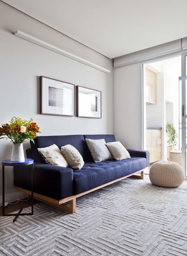 Sala minimalista e aconchegante do Apartamento da Cátia. Composição de tons neutros com o Sofá Nino azul com pés de madeira do Fernando Jaeger, Tapete ByKamy e arandela da Reka. Mesinha lateral, quadros e puff combinam com o resto da sala.