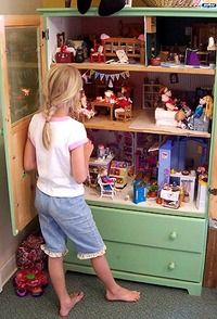 Turn a dresser or armoire into a gigantic doll house and use drawers to store clothes, accessories, and dolls. so wish i had this!! i love how this one has doors on the front, so you can close it and make the room look tidy without disturbing how the girls had their barbie house set up!!! brilliant!!