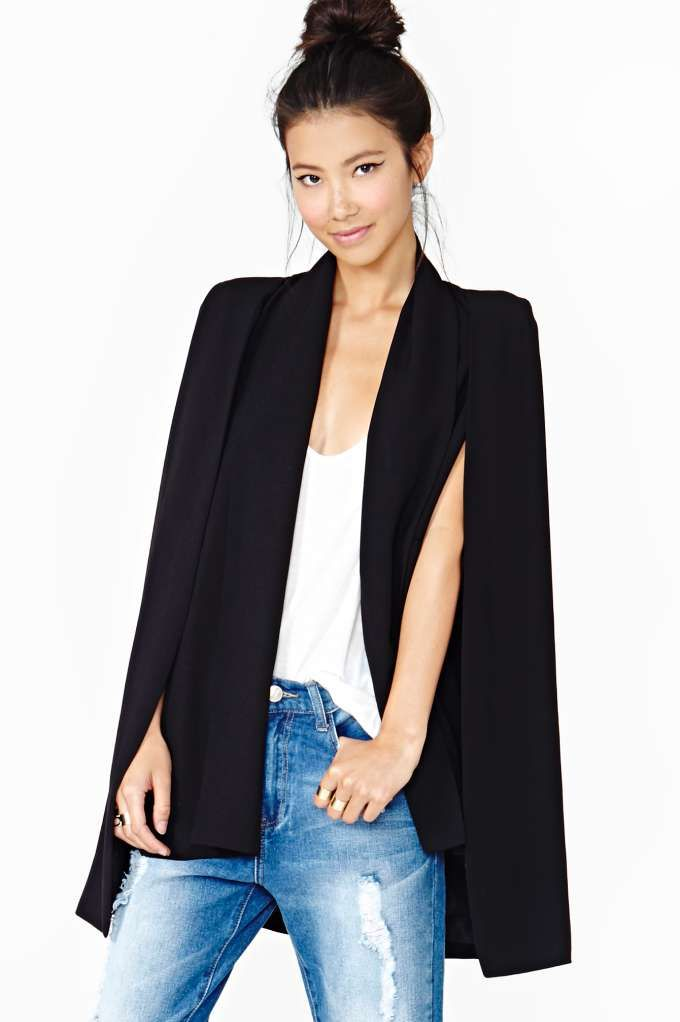 Beyond cool black cape blazer featuring slit sleeves with long-line drapey cape detailing. Fully lined, front faux pockets. Oversized fit, lightly padded shoulders. By Elliatt.