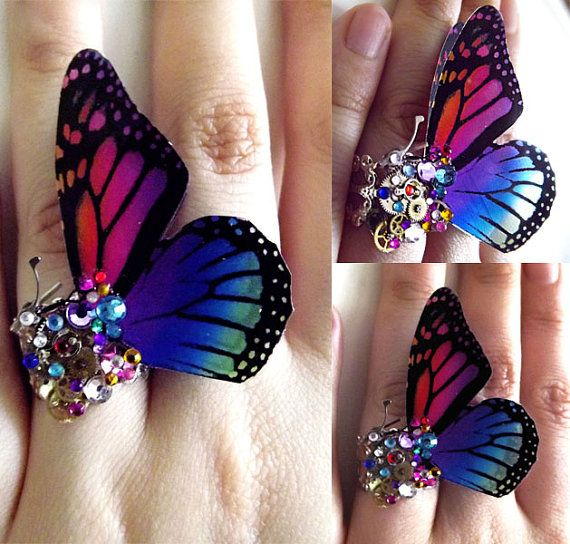 This listing is for a custom made Steampunk butterfly ring. These rings are breathtaking to look at and are highly unique.  I can design for you a special piece to call your own, using any colors you wish.  I use silver filigree for the base (which is adjustable and will fit any size finger), colored crystals in varying sizes, vibrant acrylic printed wings, charms and polished clock and watch parts.  Please let me know via etsy convo or in the notes to seller box, the color theme you would…