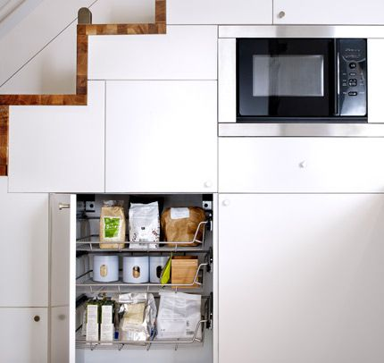 Open kitchen cabinet with wire baskets