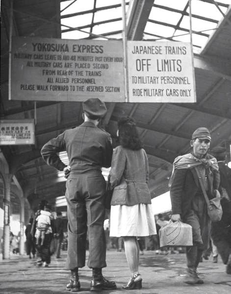 A US soldier and his Japanese girlfriend reading military restrictions about riding trains. Photograph by John Florea. Japan, 1946.