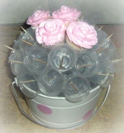 use toothpicks and clear cups to hold cupcakes in place to make a cupcake bouquet