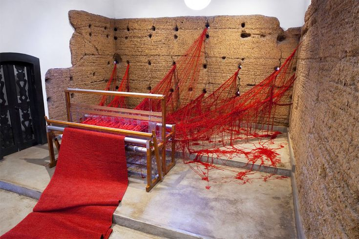 """En 2011, l'artiste brésilienne """"Tatiana Blass"""" a percé les murs d'une chapelle à Sao Paulo pour y amasser des tonnes de fil rouge. L'installation, intitulée Penelope, a été nommé ainsi en référence à l'épouse d'Ulysse dans l'Odyssey d'Homer. Elle qui se tenait loin des prétendants, alors qu'il était en guerre, en tissant un linceul"""