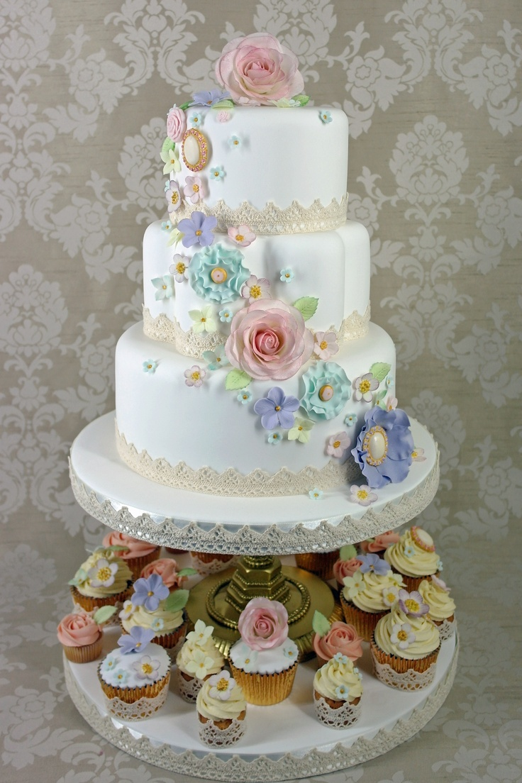 Vintage flower and brooch cascade with coordinating cupcakes #wedding cake